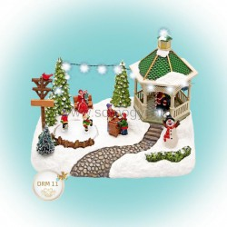 Világító karácsonyi falu, korcsolyázó gyerekekkel